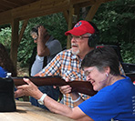 Photo of Bruce Mikesell, certified instructor watching as first time shooter Katheleen Nealeigh of Greenville, OH, as she aims.